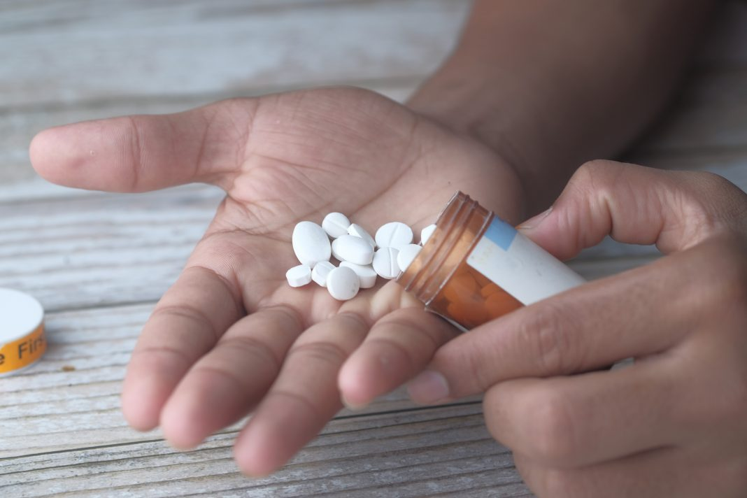 Man taking more sleeping pills.  opioid and drug abuse concept